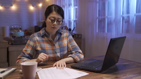 beautiful asian korean business lady work day and night. woman in casual wear sitting at dark home kitchen type on laptop computer and counting on calculator with document papers. female hardworking