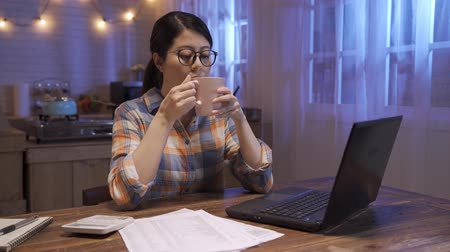 young businesswoman using calculator and laptop for calculating finance and tax in home kitchen. office lady accounting statistics and analytic research concept. female worker drink tea at night Dostupné videozáznamy
