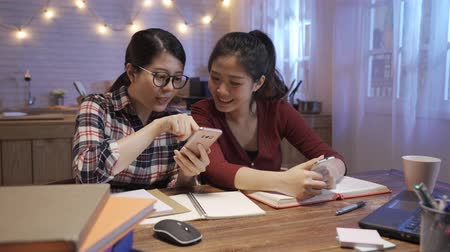 two girl friends sitting at kitchen table and looking at mobile phone. Group female people students watching video on smartphone and discussing. women enjoy break time during doing homework in night