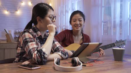 Group of happy asian chinese girl friends having fun in home kitchen at night. Trendy young female people enjoying time together playing music and reading sheet on digital tablet. Youth concept.