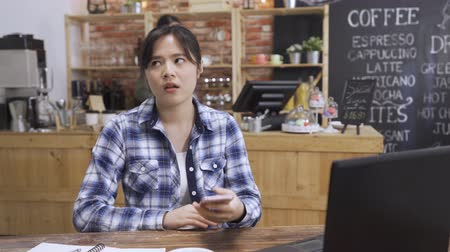 stressful college girl angry and mad at smartphone in cafe. student discussing on cellphone disagree with teamwork partner on project hang up phone and typing message. waitress make coffee in counter Wideo