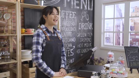 back view of young woman customer ordering at wooden counter in cafe store. friendly waitress in apron standing in coffee shop at morning smiling and greeting to client while using tablet on table.