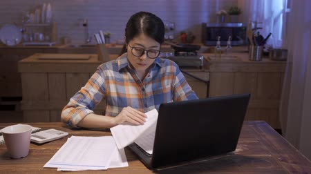 asian chinese young businesswoman working on laptop at home kitchen late into night. office lady overwork after back to house in midnight. female worker reading document paper and typing on keyboard Wideo