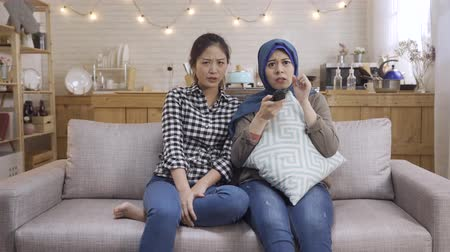 two scared asian muslim and korean women friends in living room sofa watching horror movie looking at terrible plot feeling fearful and shocked. diverse college roommates relax together in dormitory
