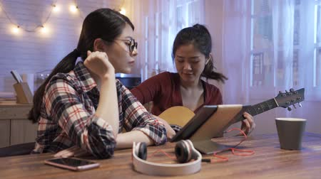 Mixed race young woman with tablet computer sitting at dining table in dark kitchen teaching her sister to play acoustic guitar at home. young girl friends discussing on sheet on pad writing song. Wideo
