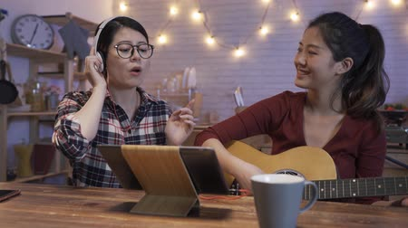 two asian korean girl friends playing guitar and singing indoors at late night. young ladies roommates love music having fun in dark kitchen at midnight. female with headphones and tablet write song
