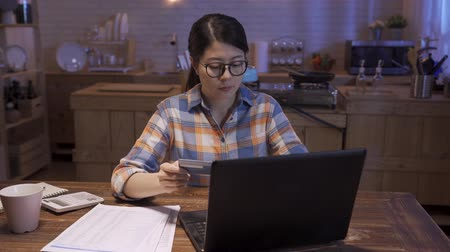 young female start up business owner sitting at wooden kitchen at home in night. confident woman boss smiling and working on company finance. beautiful lady holding credit card paying tax on laptop.
