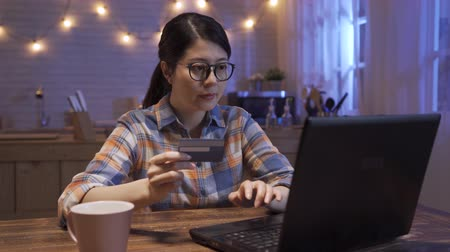 Young confident pretty asian korean woman in glasses paying online website with laptop and credit card at home. happy lady smiling while shopping on internet summer sale in dark home kitchen at night Wideo