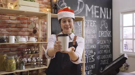 merry christmas concept. elegant female waitress in red santa hat giving paper cup of tea face camera smiling. asian korean woman bartender serving coffee while standing in modern cafe store Wideo