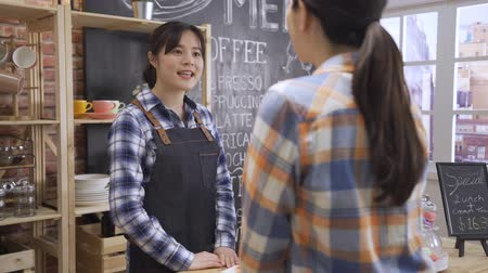 back view of female customer ordering to waitress in apron at counter in bright coffee shop. young girl bartender using point of sale terminal listening to client patiently and asking personal flavor