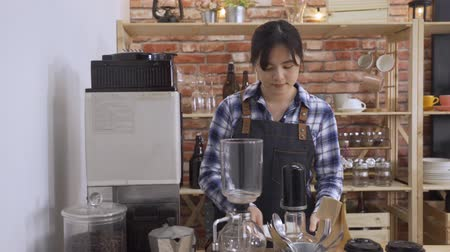 beautiful asian chinese barista preparing coffee at coffee-shop. lady using professional machine making beverage for customer order in cafe store. elegant female bartender in apron working in counter