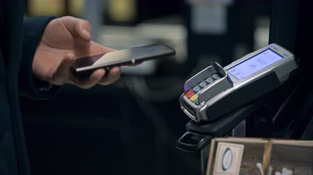 плата : Contactless payment with your smartphone. Paying with a smartphone device on a credit card terminal. Wireless payment