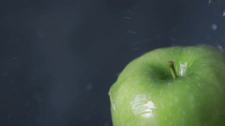 legal : Pouring water on tasty green apple, slow motion