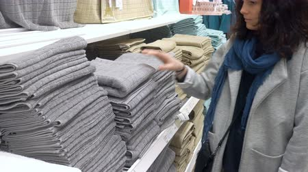 towel folded : MOSCOW, RUSSIA, MAY 20, 2016: Woman Choosing Grey Terry Towel In Department Store