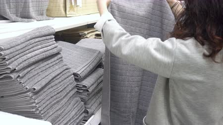short clip : MOSCOW, RUSSIA, MAY 20, 2016: Woman Choosing Grey Terry Towel In Department Store