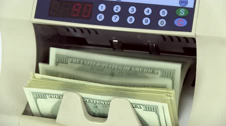 counter : Cash money counting machine. Banknote counter are counting hundred dollar bills. Close-up