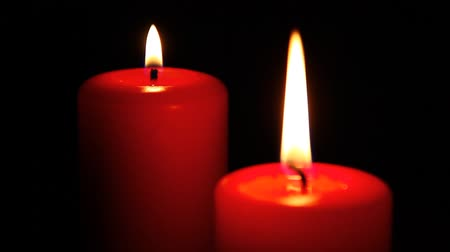 valentin nap : A pair of red candles on total dark background.