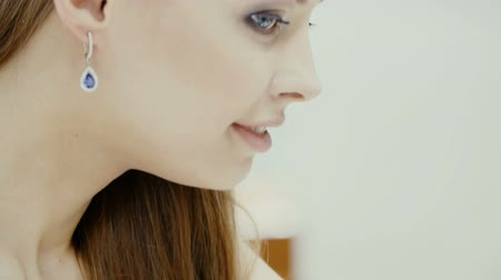brincos : Lovely girl wears jewelry in the bathroom. Stock Footage
