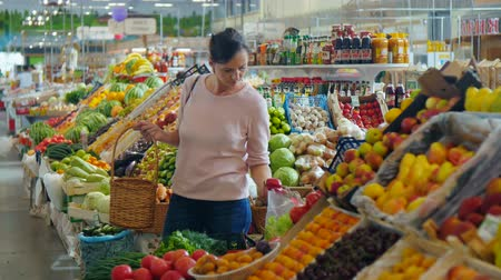 супермаркет : Girl chooses vegetables in a supermarket .