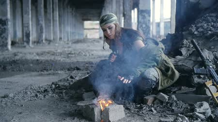 bojování : girl in military uniform, heated by the fire in the destroyed building