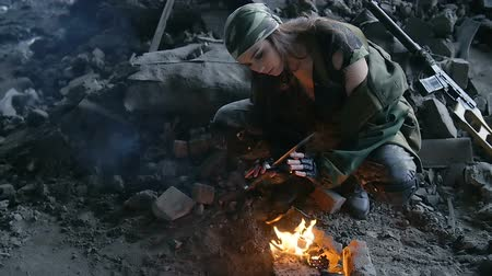 harcos : girl in military uniform, heated by the fire in the destroyed building