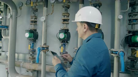 осмотр : engineer inspects the gas boiler