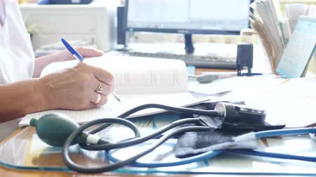 complaints : the doctor records the diagnosis in the journal. Close-up
