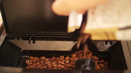 dark roast : The grain of coffee is pouring into the coffee machine, close-up