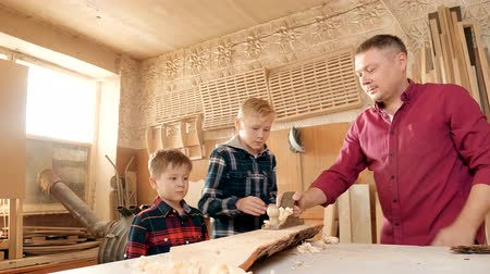 workman : family, carpentry, woodwork and people concept. father teaches son carpentry.