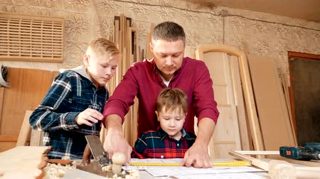 плотничные работы : family, carpentry, woodwork and people concept. father teaches son carpentry.