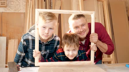 workman : Father is a carpenters workshop son. Friendly family indoors, funny portrait.