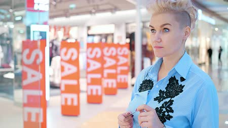 Concept of a woman with a bank card is thinking about buying in a mall. A sign of the sale in the store. Stockvideo