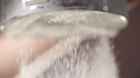 pekař : Slow motion shot of sifting flour through sieve.