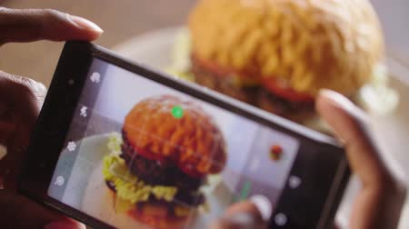 étkező : Cell phone photographing a burger. Hamburger on cafe table Stock mozgókép