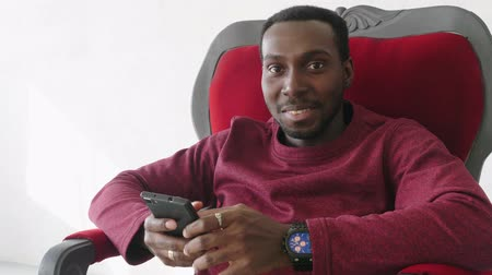 afro amerikan : black man uses a smartphone to communicate on the Internet.