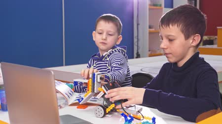 constructing : Children creating robots at school, stem education. Early development, diy, innovation, modern technology concept.