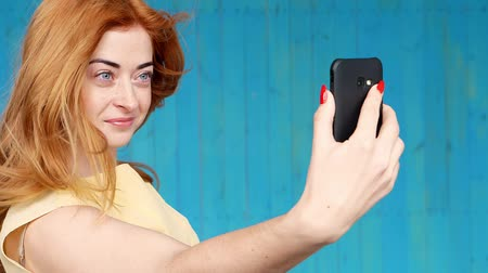 rty : Photo of cheerful young redhead lady standing isolated over white wall background. Looking camera make selfie.