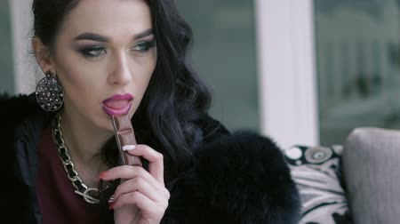 biała czekolada : Glamorous brunette sitting, looking aside and touching chocolate by lips. Slowly