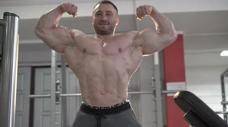 vencedor : The world champion of bodybuilding posing in the gym. Slowly