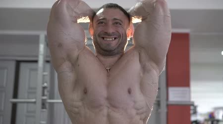torzó : Muscular bodybuilder in gym posing on the camera. Slowly