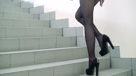 longo : Sexy long legs going upstairs in fashion shoes and tights. Slowly