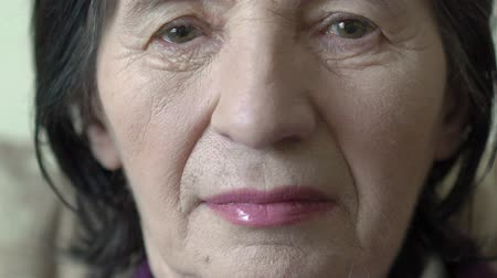 head portrait : Closeup face of old woman looking on a camera. Slow motion Stock Footage