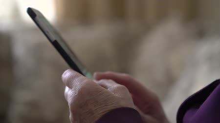 olhares : Smartphone in old womans hands with wrinkles on a window background