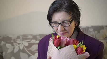 сюрприз : Closeup portrait of woman in her 70s holding the bouquet of flowers and smiling