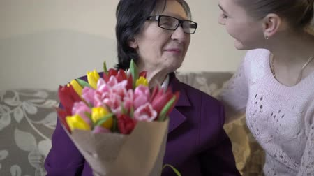 den matek : Happy cute girl giving flowers her business grandmother in her 70s.
