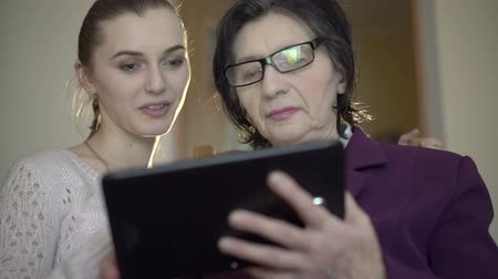 starość : Elegant old business woman and young girl using a tablet on the room background Wideo