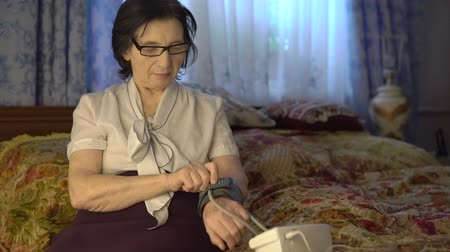 self examination : Old pleasant woman putting blood pressure measurement tool on hand. Stock Footage