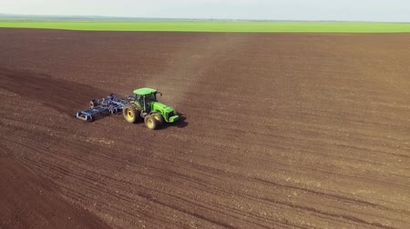 tractor trailer : Aerial view of tractor cultivating fields soil in spring day