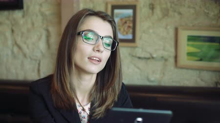 perfil : Pretty young woman taking glasses and using tablet in cafe. 4k