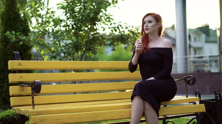 fumegante : Portrait of passionate woman smoking in black dress, sitting on a bench in 4k